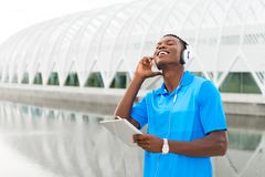 Student with Digital Tablet. Black, African American college student wearing headphones and listening to music on a digital tablet computer Royalty Free Stock Image