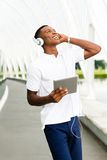 Student with Digital Tablet. Black, African American college student wearing headphones and listening to music on a digital tablet computer Stock Photos