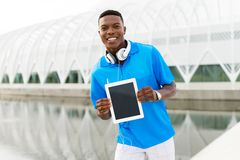 Student with Digital Tablet. Black, African American college student wearing headphones and showing a digital tablet computer Stock Photo