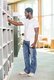 Student With Digital Tablet Choosing Book In. Full length of African American student with digital tablet choosing book in bookstore Royalty Free Stock Images