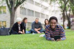 Student With Digital Tablet On Grass At Campus. Portrait of student holding digital tablet on grass at campus park with friends studying in background Stock Photos