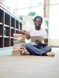 Student With Digital Tablet In Library. Full length portrait of African American male student with digital tablet and stacked books sitting on floor at library Stock Image