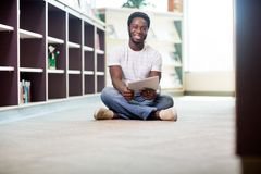 Student With Digital Tablet Sitting In Library. Full length portrait of African American male student with digital tablet while sitting on floor at library Royalty Free Stock Photo