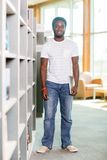 Student With Digital Tablet Standing By Bookshelf Stock Photo