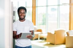 Student With Digital Tablet Standing In Library. Portrait of smiling male student with digital tablet standing in library Stock Image
