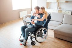 Student with disability sitting on wheelchair. Cheerful woman stand behind and embrace him. Looking on laptop. Young man royalty free stock image