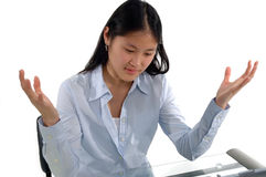 Student Dismay. A female student at her desk with hands up expressing dismay royalty free stock photography