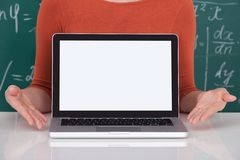 Student displaying laptop with blank screen in classroom Stock Photo