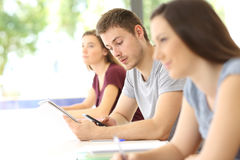 Student distracted with a phone during a class Royalty Free Stock Photography
