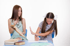 The student does not wish to learn. The teacher is angry with the student sitting with him at the table stock images