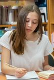 Teenage girl studying in a library. Student doing her homework in the school library royalty free stock photos