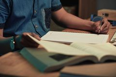 Student doing homework. Close-up image of student writing composition or essay in textbook Stock Photography