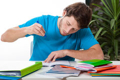 Student doing homework. A handsome student concentrated on doing his homework for college royalty free stock photos