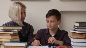 Student doing homework with the help of a tutor. stock video