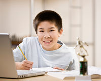 Student doing homework and using laptop. Determined student doing homework and using laptop royalty free stock image