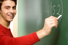 Student Doing Math on Chalkboard. Male Student Doing Math on Chalkboard Royalty Free Stock Photo
