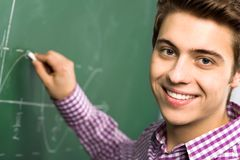 Student Doing Math on Chalkboard. Male Student Doing Math on Chalkboard Royalty Free Stock Photos