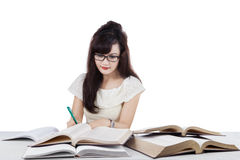 Student doing school task while writing on the book Royalty Free Stock Photos