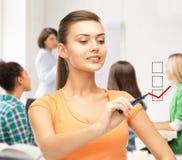 Student drawing checkmark on virtual screen Royalty Free Stock Photos