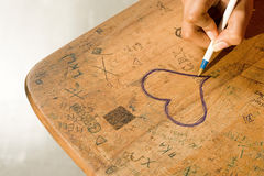 Student drawing a heart on her desk Royalty Free Stock Image