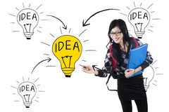 Student drawing lightbulb symbolizing idea stock image