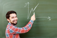 Student draws graph on blackboard Royalty Free Stock Photos