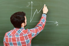 Student draws graph on blackboard. Graphs and diagrams. Young male student in plaid shirt drawing a graph on a blackboard in classroom Stock Photography