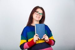 Student dreamer. Young student dreamer wearing glasses and holding a book thoughtful looking up over grey wall background royalty free stock image
