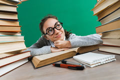 Student dreaming or thinking of something pleasant while sitting at the desk with open book Royalty Free Stock Photos