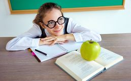 Student dreaming or thinking of something pleasant while sitting at the desk with open book, looks away. royalty free stock images