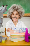 Student dressed up as einstein using a chemistry set Royalty Free Stock Image