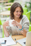 Student drinking coffee while using laptop at cafeteria table Stock Images