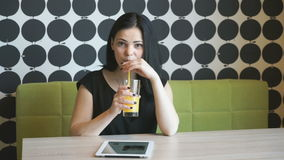 Student drinks orange juice indoors. Student girl aged 20s drinks orange juice and poses for camera indoors stock video