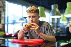 A student eats fast food in a bistro. An appetizing burger in the hands of a young man. A look at the camera. stock photography