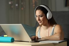 Student elearning watching online tutorials in the night. Student elearning wearing headphones watching online tutorials in the night at home royalty free stock images