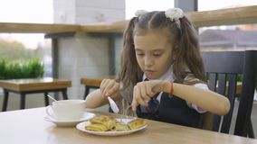 Student elementary school eating in the cafeteria alone. Student elementary school in a school uniform sitting at a table in the school cafeteria and eat stock footage