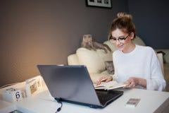 Student eller freelancer som hemma arbetar med bärbara datorn Den charmiga unga kvinnan sitter framme av bildskärmen a med notepa arkivfoto