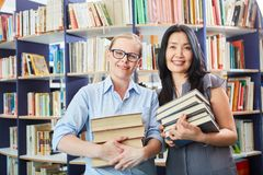 Student en bibliothecaris met boekenstapel stock fotografie