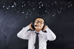 Student enjoy music with headphones. Male elementary school student enjoy music with headphones in the classroom Stock Photos