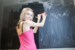 Student erasing the chalkboard/blackboard Stock Photo