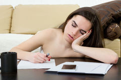 Student ermüdete und schlafend in ihrem Wohnzimmer über den Anmerkungen Stockbilder