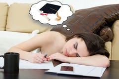 Student ermüdete und schlafend in ihrem Wohnzimmer über den Anmerkungen Stockfoto