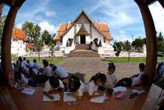 Student excursions in temple. NAN,THAILAND-SEPTEMBER 27,2011: Groups of local school boy and girl dressed with a traditional native read a book outside Buddhist Stock Photo
