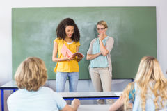 Student explaining notes besides teacher in class Stock Photography
