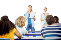 Student explaining notes besides teacher in class. Female student explaining notes besides teacher in the class Stock Image