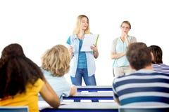 Student explaining notes besides teacher in class Stock Image