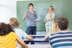 Student explaining notes besides teacher in class Stock Photos