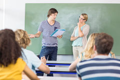 Student explaining notes besides teacher in class Stock Photo