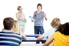 Student explaining notes besides teacher in class. Male student explaining notes besides teacher in the class Royalty Free Stock Photo