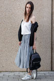 Student för ung kvinna för brunett med ryggsäcken i tillfällig stil arkivfoto